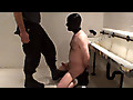 Kneeling on the wetroom floor, mostly naked except for boots, a hood and his chains